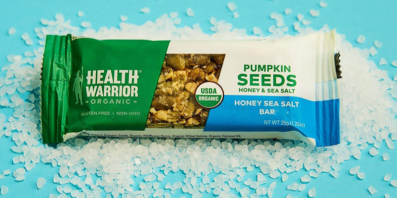 Health Warrior protein bar surrounded by salt grains