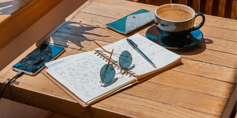 notebook, coffee and sunglasses on the table
