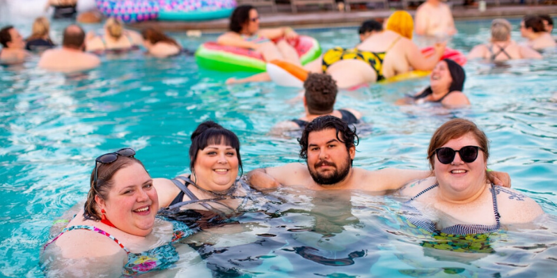 a group of 4 plus size people posing in the pool