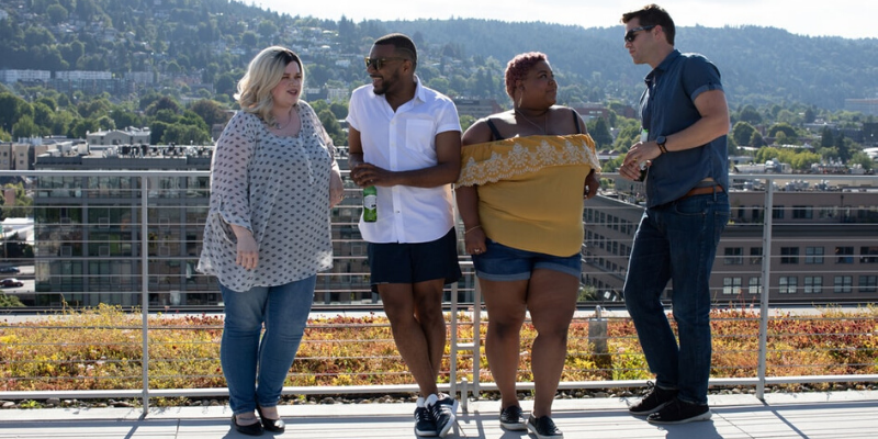 a group of four plus size people posing outside