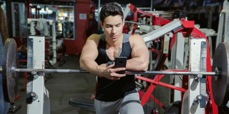 a man looking at his cellphone while supporting himself on gym equipment