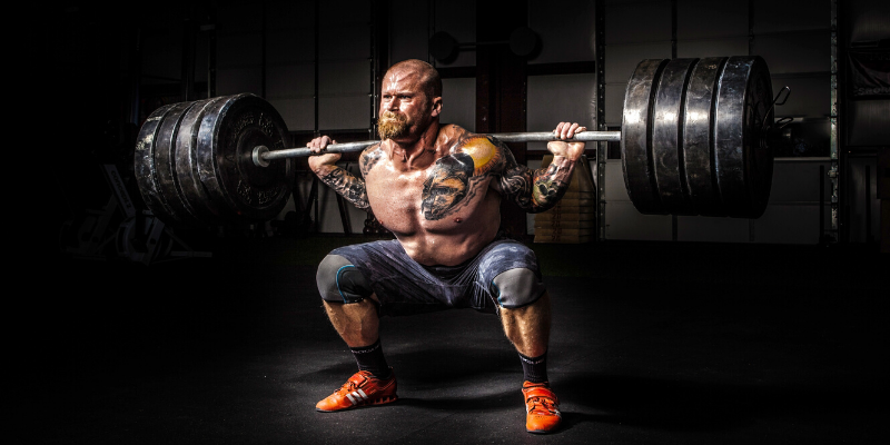 a muscled man lifting a very heavy barbell