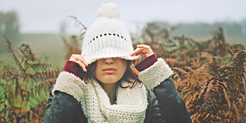 a woman pulling her winter hat on her eyes