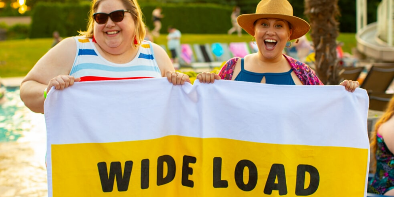 two plus size woman holding a sign 'wide load'