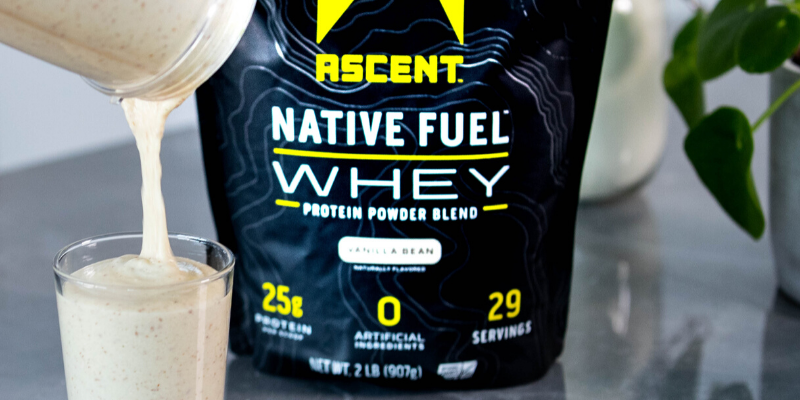 a bag of ascent protein and a glass of protein shake being poured