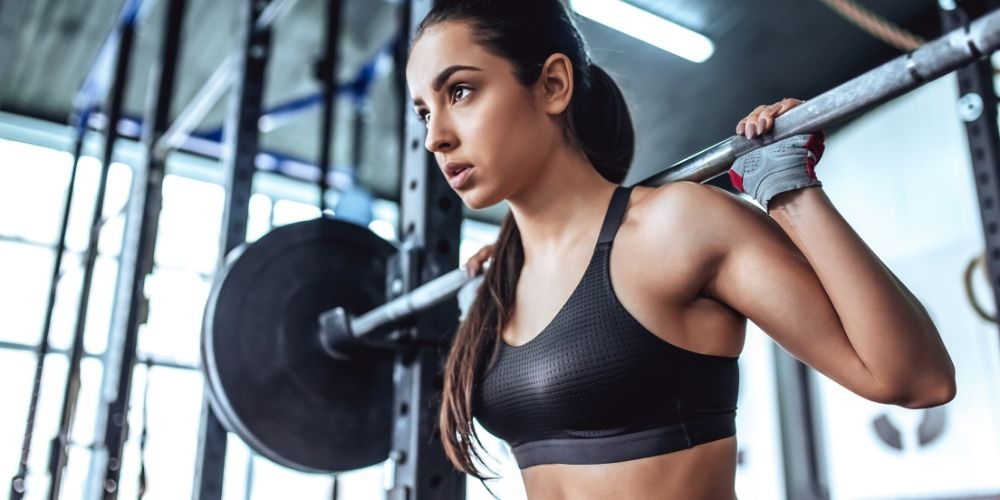 woman with barbells in power rack