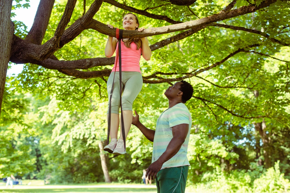 woman doing pull-up assisted by her fitness coach on tree